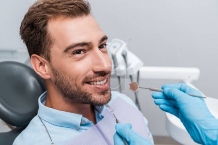 Photo pour Vue recadrée du dentiste dans des gants de latex retenant des instruments dentaires près du patient - image libre de droit
