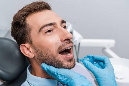 Photo pour Vue recadrée de dentiste dans les gants bleus de latex retenant le dispositif de retenue près de l'homme barbu - image libre de droit