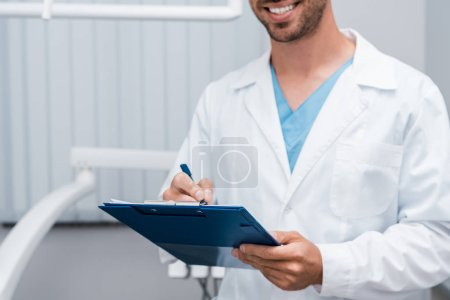 Photo for Cropped view of happy bearded doctor holding clipboard and pen in clinic - Royalty Free Image