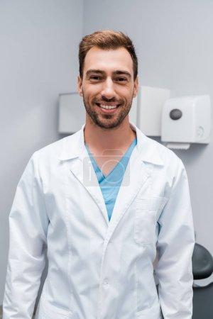 Photo pour Docteur barbu heureux dans le manteau blanc regardant l'appareil-photo tout en restant dans la clinique - image libre de droit