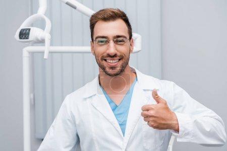 Photo pour Médecin heureux dans des lunettes montrant pouce vers le haut à la clinique - image libre de droit
