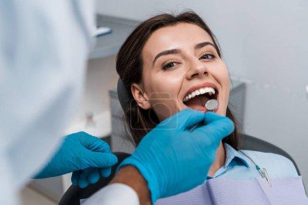 Photo pour Foyer sélectif du dentiste dans des gants en latex tenant miroir dentaire près de la femme - image libre de droit