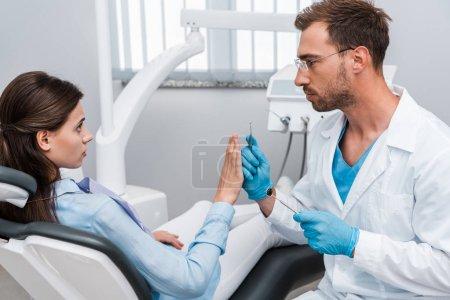 Photo pour Beau dentiste barbu tenant des instruments dentaires et regardant la femme effrayée faisant des gestes dans la clinique - image libre de droit