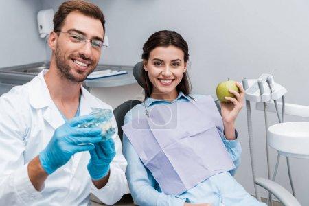 Photo pour Foyer sélectif du dentiste gai dans le modèle de dents de fixation de glaces près de la femme heureuse avec la pomme verte - image libre de droit