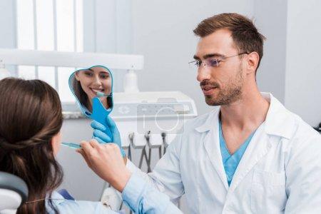Photo pour Foyer sélectif de la fille se brossant des dents et regardant le miroir près du dentiste beau - image libre de droit