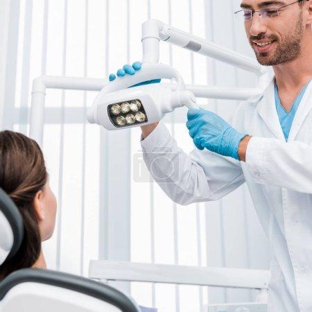 Photo pour Foyer sélectif du beau dentiste dans des gants de latex touchant la lampe médicale près du patient - image libre de droit