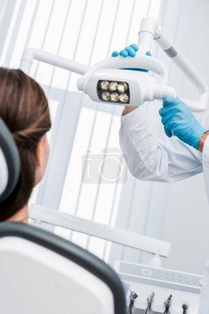 Photo pour Vue recadrée du dentiste dans des gants de latex touchant la lampe médicale près du patient - image libre de droit