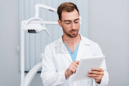 Photo for Handsome man in white coat and glasses using digital tablet in clinic - Royalty Free Image