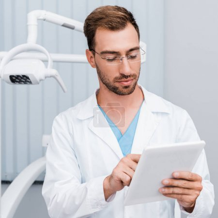 Photo for Handsome bearded man in white coat and glasses using digital tablet - Royalty Free Image