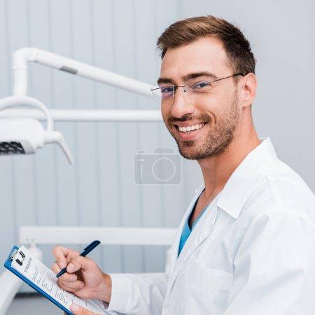 Photo pour Homme barbu heureux dans le manteau blanc et les glaces retenant le stylo et le presse-papiers dans la clinique dentaire - image libre de droit