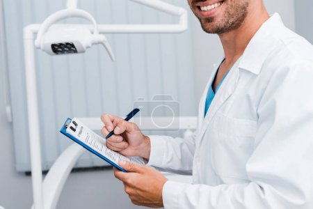 Photo for Cropped view of bearded man in white coat holding pen and clipboard in dental clinic - Royalty Free Image