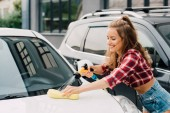 cheerful girl holding pressure washer and sponge while washing car