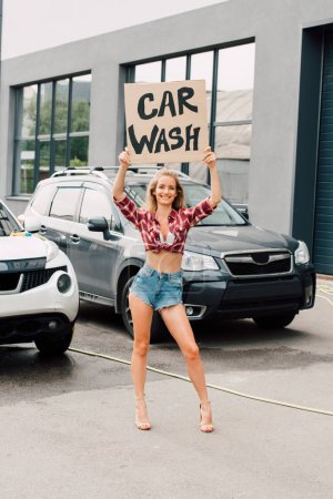 Photo for Cheerful young woman standing and holding carton board with car wash lettering near cars - Royalty Free Image