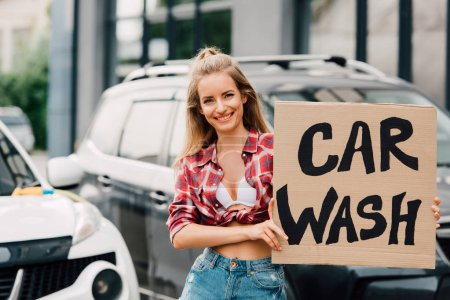 Photo for Happy girl holding carton board with car wash lettering near cars - Royalty Free Image