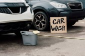 white and black cars near bucket and carton board with car wash letters