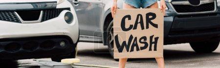 Foto de Foto panorámica de la chica de pie y sosteniendo cartel de cartón con cartas de lavado de coches cerca de los coches - Imagen libre de derechos