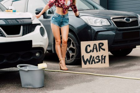 Photo for Cropped view of girl standing near cars and placard with car wash letters - Royalty Free Image