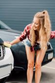 happy woman holding yellow sponge while washing car