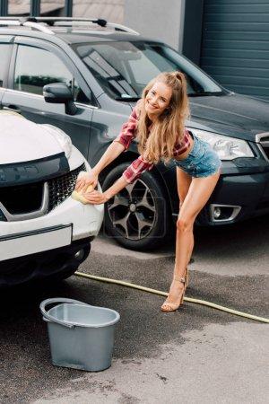 junge glückliche Frau mit gelbem Schwamm beim Autowaschen