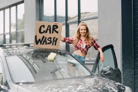 Photo for Positive young woman holding carton board with car wash lettering and standing near automobile - Royalty Free Image