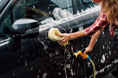 Photo for Cropped view of young woman washing wet car in foam with sponge - Royalty Free Image
