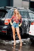 cheerful girl standing with hands on hips near autos in car wash