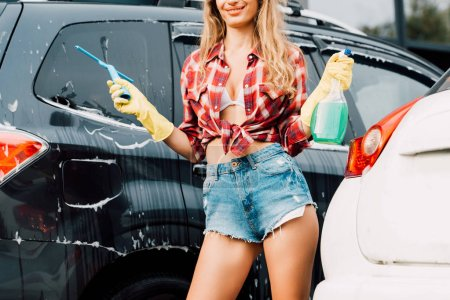 Photo for Cropped view of happy girl holding spray bottle and squeegee near cars - Royalty Free Image