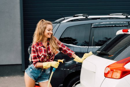 Photo for Smiling woman in latex gloves holding pressure washer - Royalty Free Image
