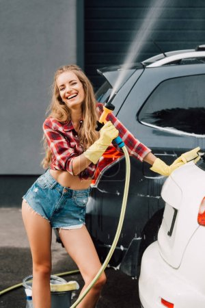 Photo for Cheerful girl holding pressure washer and smiling near autos - Royalty Free Image