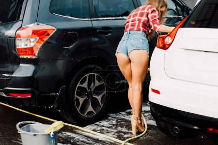 Photo for Sexy girl standing near white and black cars and bucket with sponge - Royalty Free Image