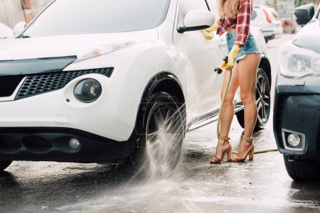 cropped view of woman standing and washing car with pressure washer