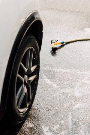 Photo pour Voiture de luxe blanche et moderne près de la rondelle de pression sur l'asphalte - image libre de droit