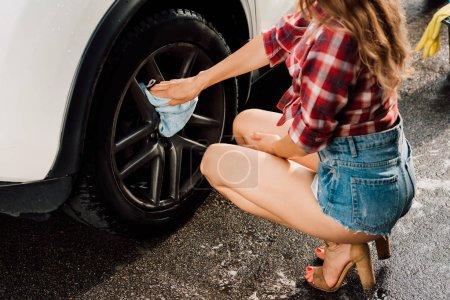 Photo for Cropped view of girl holding blue cloth and washing car - Royalty Free Image
