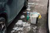 selective focus of luxury car near bucket with water and spray bottle