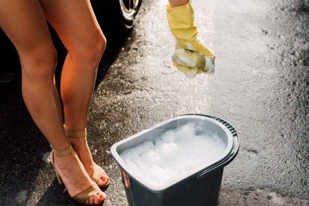 Foto de Vista recortada de la mujer sosteniendo esponja en espuma cerca de cubo con agua - Imagen libre de derechos