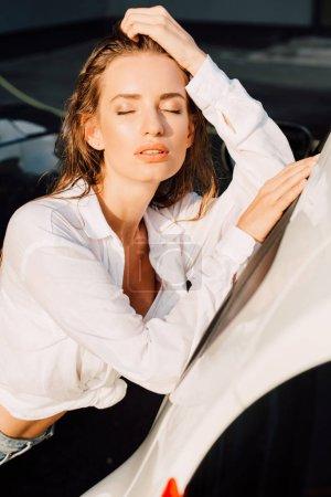 Photo pour Attrayant femme fermé les yeux tout en se tenant près de voiture blanche - image libre de droit