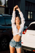 attractive young woman with closed eyes standing near modern cars