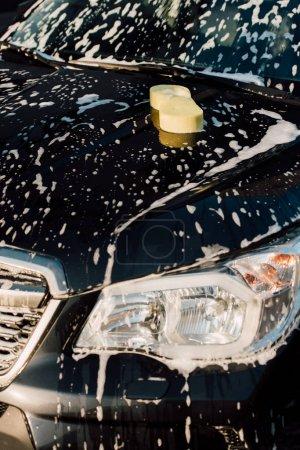 Photo pour Éponge jaune sur la voiture noire humide et de luxe dans la mousse - image libre de droit