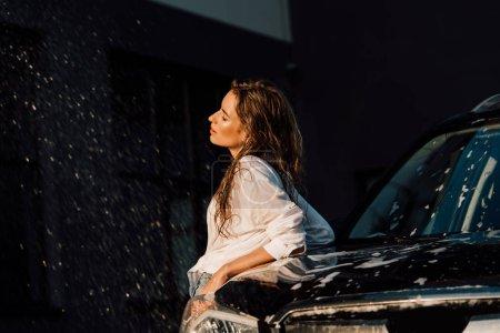 Photo pour Fille attirante et humide restant près de la voiture noire de luxe - image libre de droit