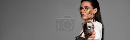 panoramic shot of confident steampunk woman aiming with pistol at camera isolated on grey