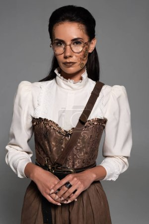 attractive steampunk woman in glasses with makeup isolated on grey