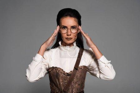 Photo pour Vue de face de la femme steampunk avec des lunettes de maquillage touchantes isolées sur gris - image libre de droit