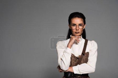 vue de face de coûteux steampunk fille dans des lunettes isolées sur gris