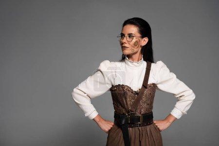 Foto de Mujer steampunk pensativa en gafas de pie con las manos en las caderas aisladas en gris - Imagen libre de derechos