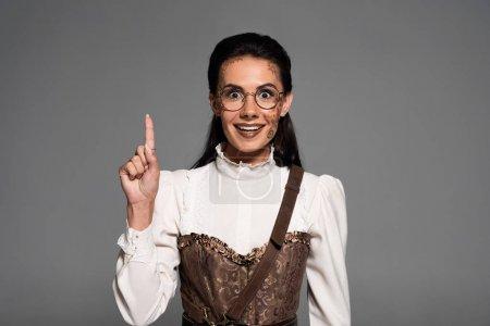 Photo pour Vue avant de la femme steampunk attirante excitée affichant le signe d'idée d'isolement sur le gris - image libre de droit