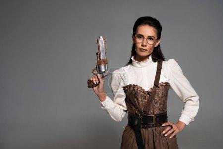 Foto de Atractiva mujer steampunk de pie con la mano en la cadera y sosteniendo la pistola aislada en gris - Imagen libre de derechos