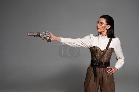 Foto de Atractiva mujer steampunk de pie con la mano en la cadera y apuntando con pistola en gris - Imagen libre de derechos
