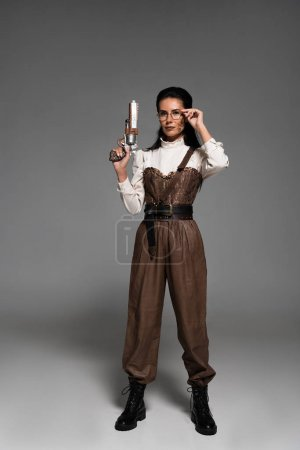 full length view of steampunk woman holding vintage pistol and touching glasses on grey
