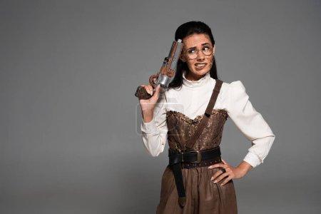 Foto de Mujer preocupada steampunk de pie con la mano en la cadera y sosteniendo pistola vintage aislada en gris - Imagen libre de derechos