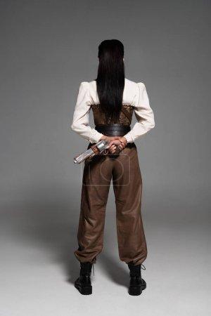 Photo pour Vue pleine longueur de femme steampunk retenant le pistolet de cru sur le gris - image libre de droit